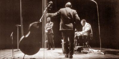 Три мужчина: со сложенными руками, с контрабасом, за ударными инструментами