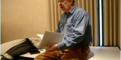 Мудчина сидит на столе и читает