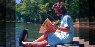Женщина читает журнал на берегу