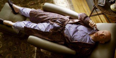 Мужчина в пижаме и халате, лежащий в кресле