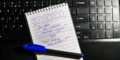 Блокнот с ручкой на клавиатуре