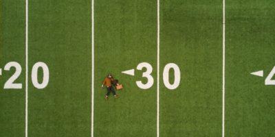 Человек лежит на зеленом поле и числа