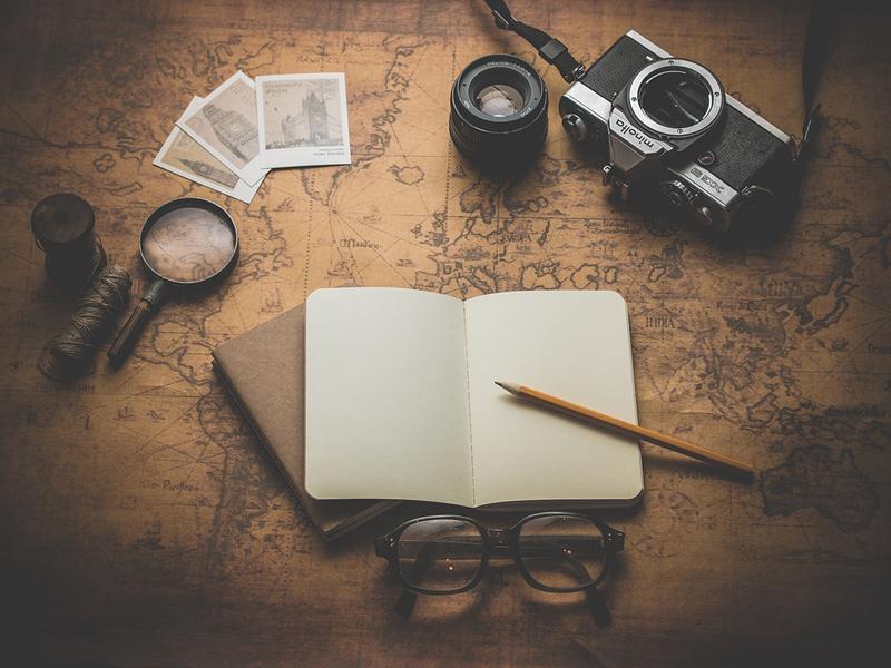 Блокнот с карандашом, фотоаппарат, очки, лупа