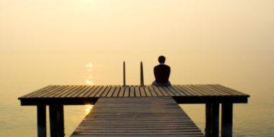 Человек сидит на мостике