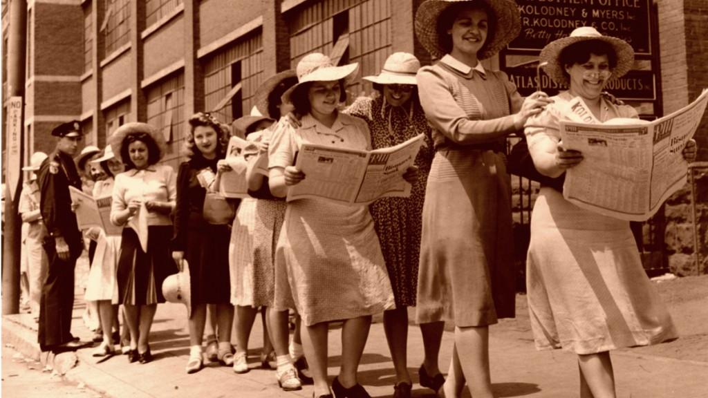 Женщины идут и читают газеты