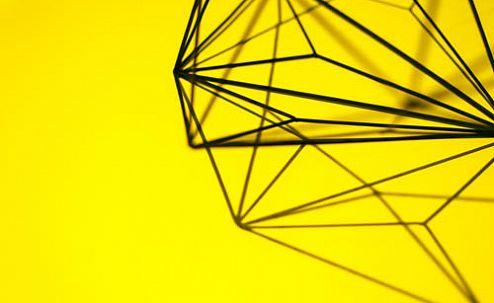На желтом фоне конструкция из проволоки